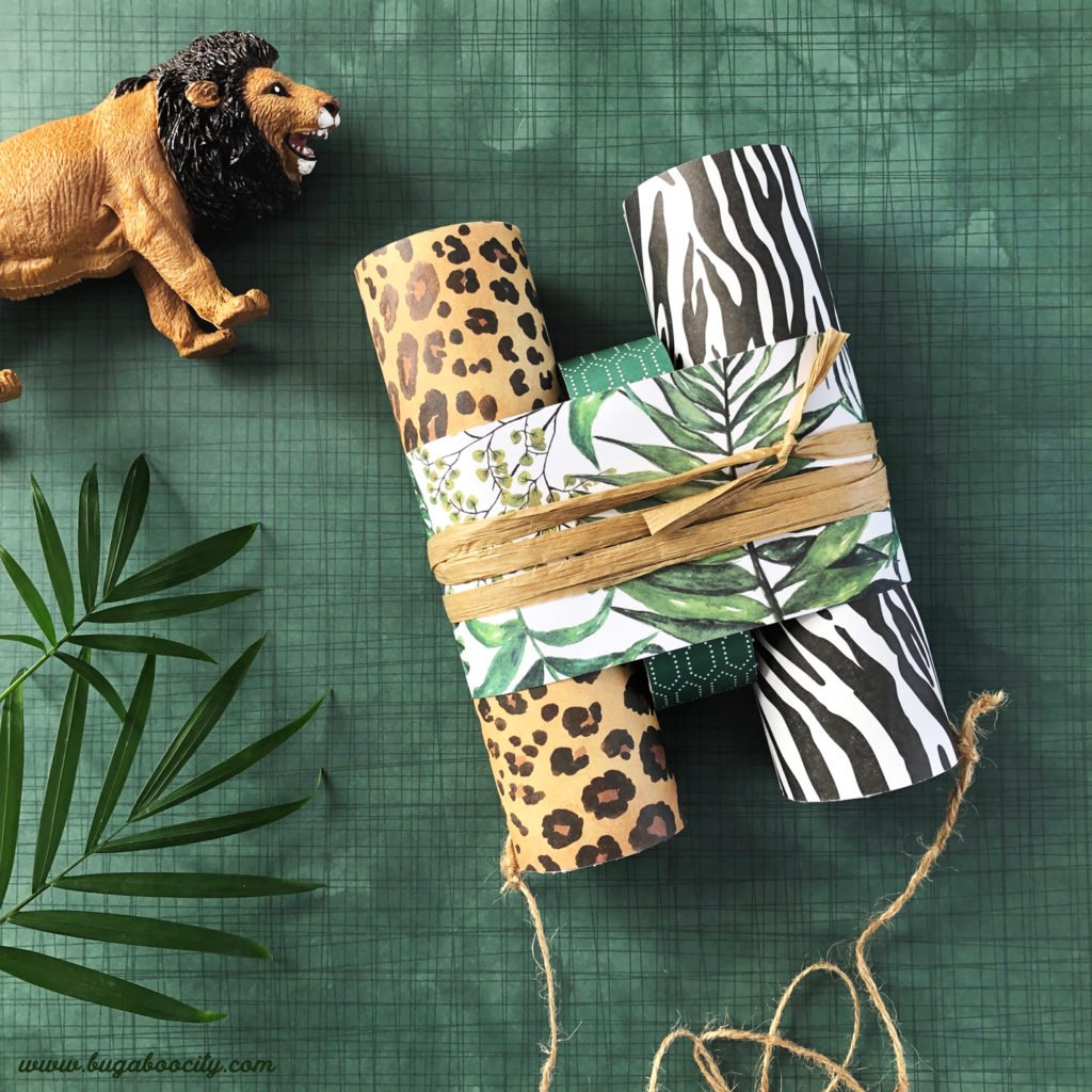 A pair of safari binoculars with a cute toy lion lay on a green background.