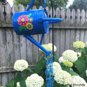 Blue watering can with colorful vinyl flowers on the side and blue and white beads coming out of the spout.
