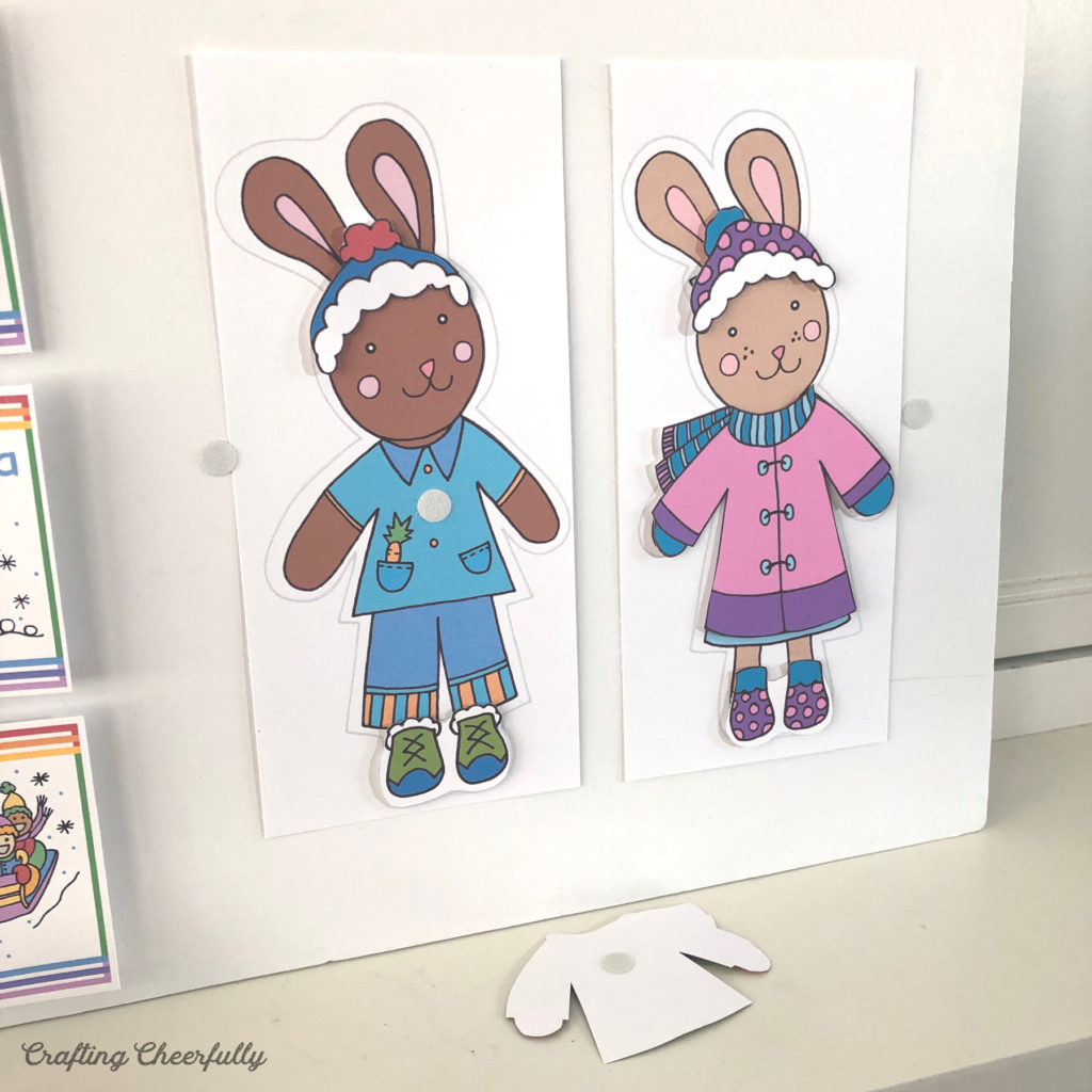 Two bunny paper dolls with Velcro Dots are displayed on a white foam board.
