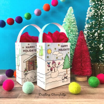 Paper gift bags colored and sitting next to Christmas trees and pom poms.