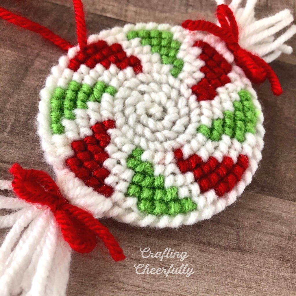 Peppermint ornaments made from a cross stitch pattern using yarn and a plastic canvas.