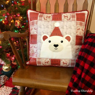 Red and white polar bear pillow sits on a rocking chair next to a Christmas tree.
