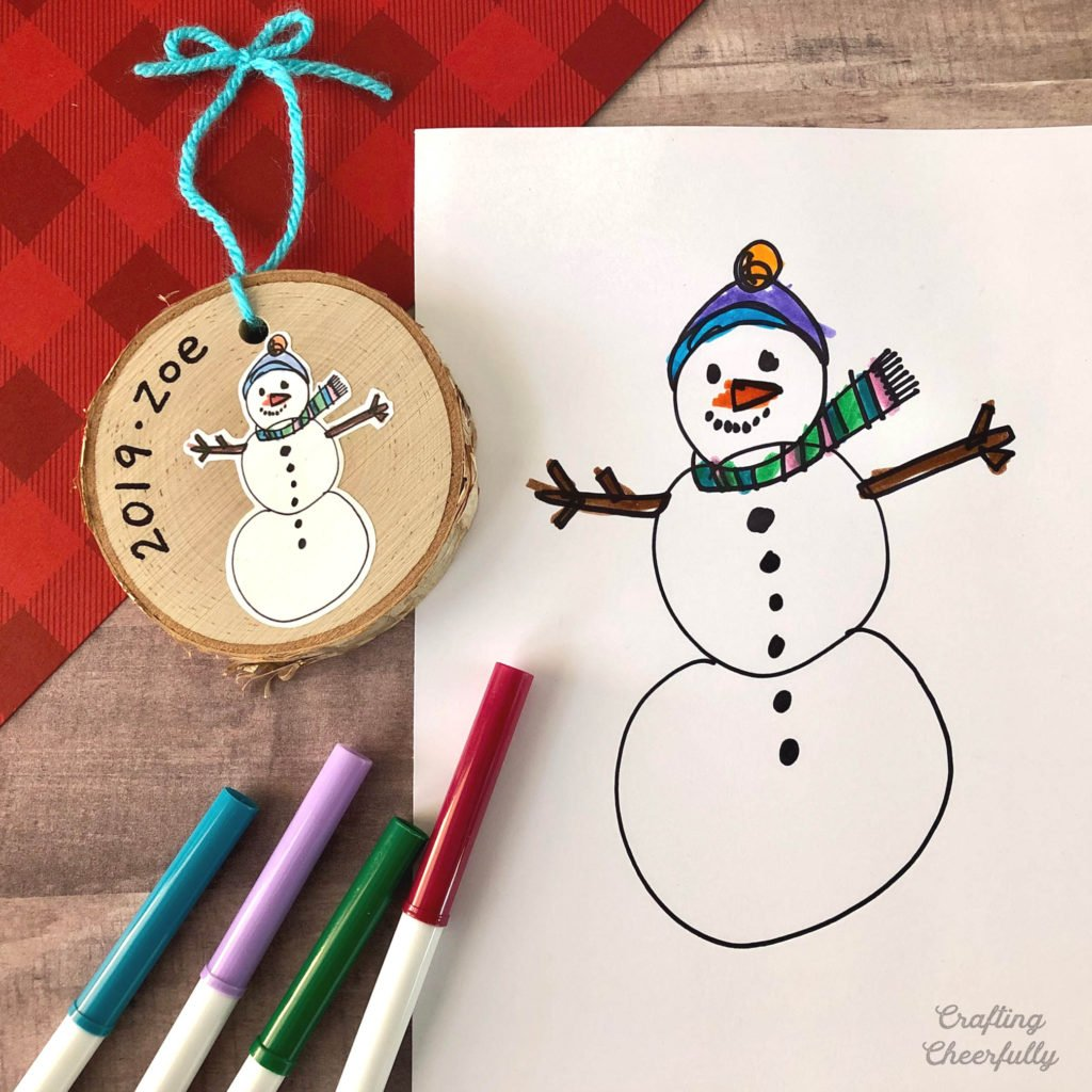 A drawing of a snowman by a child lays next to a wooden coaster ornament with the same drawing on it but smaller. The words Zoe and the date are on the ornament.
