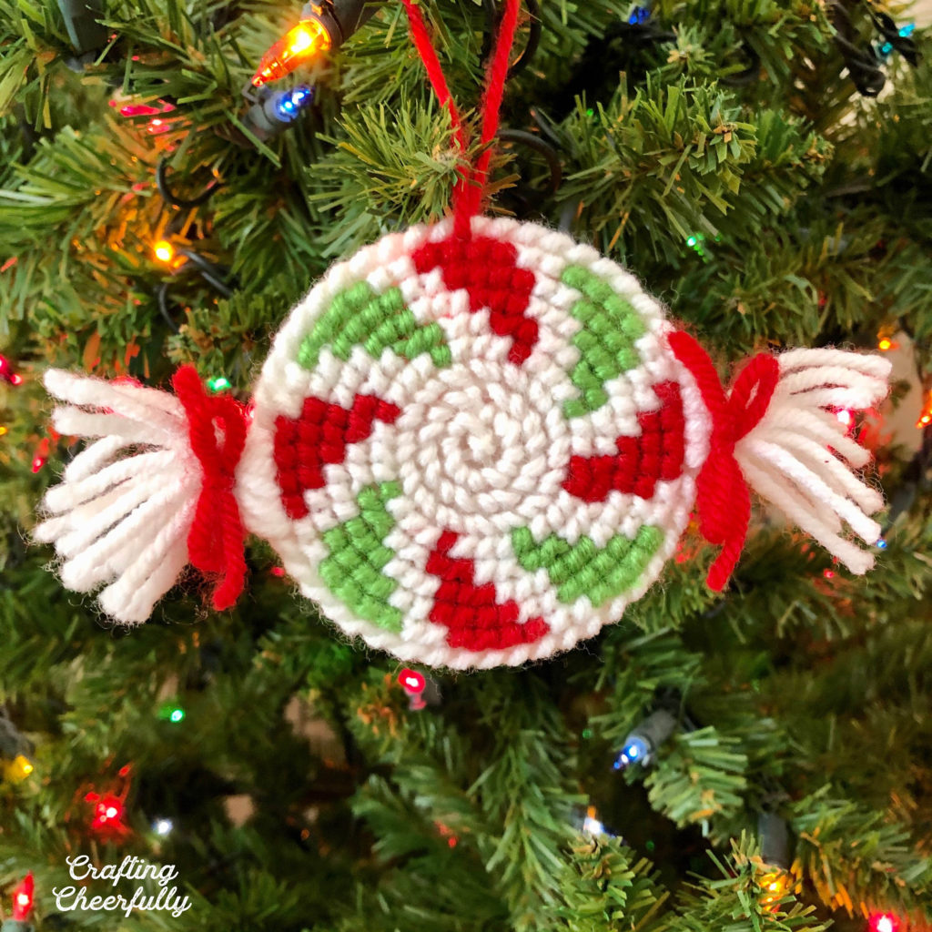 A peppermint ornament hangs in a tree. It is made from yarn and is red, green and white.