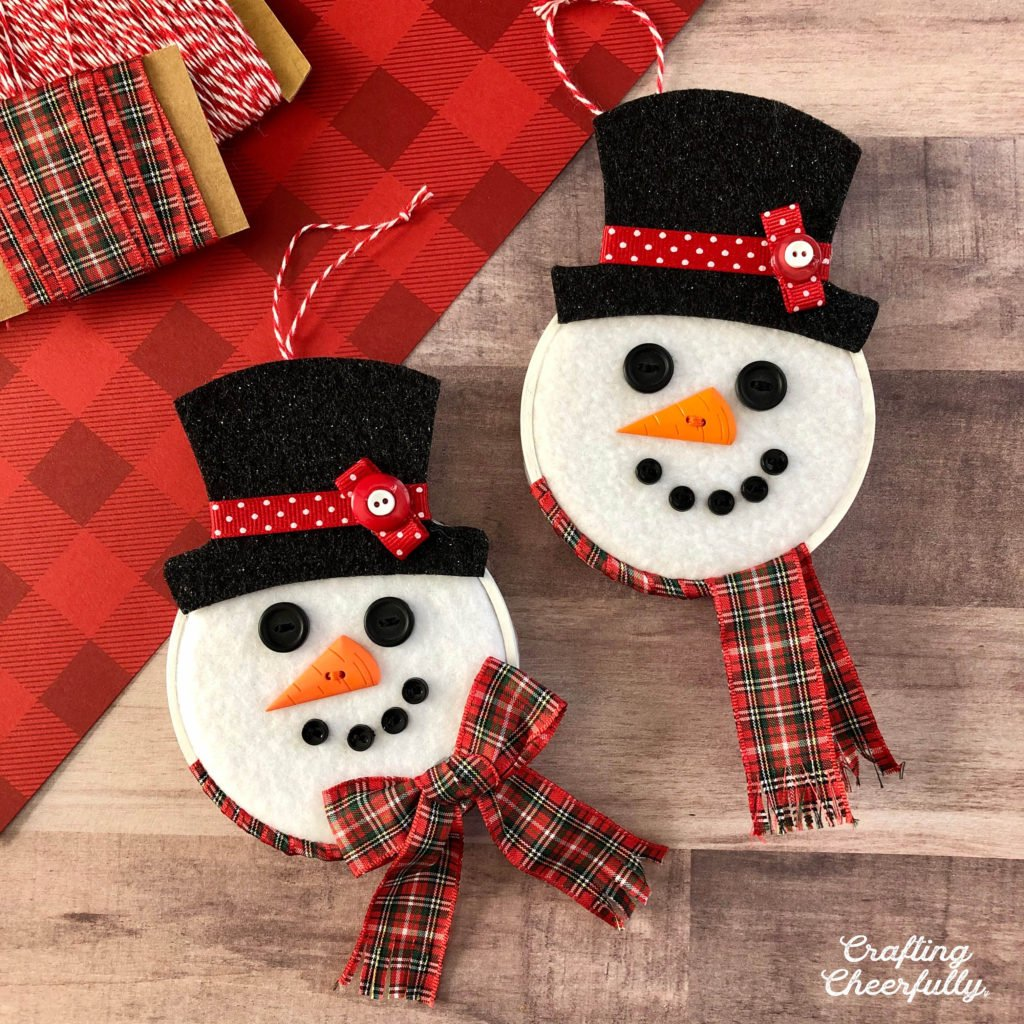 Two snowmen ornaments lay on a table next to red paper and holiday ribbon. The snowmen ornaments are made from embroidery hoops, fleece, felt and ribbon. They are cute happy snowmen.
