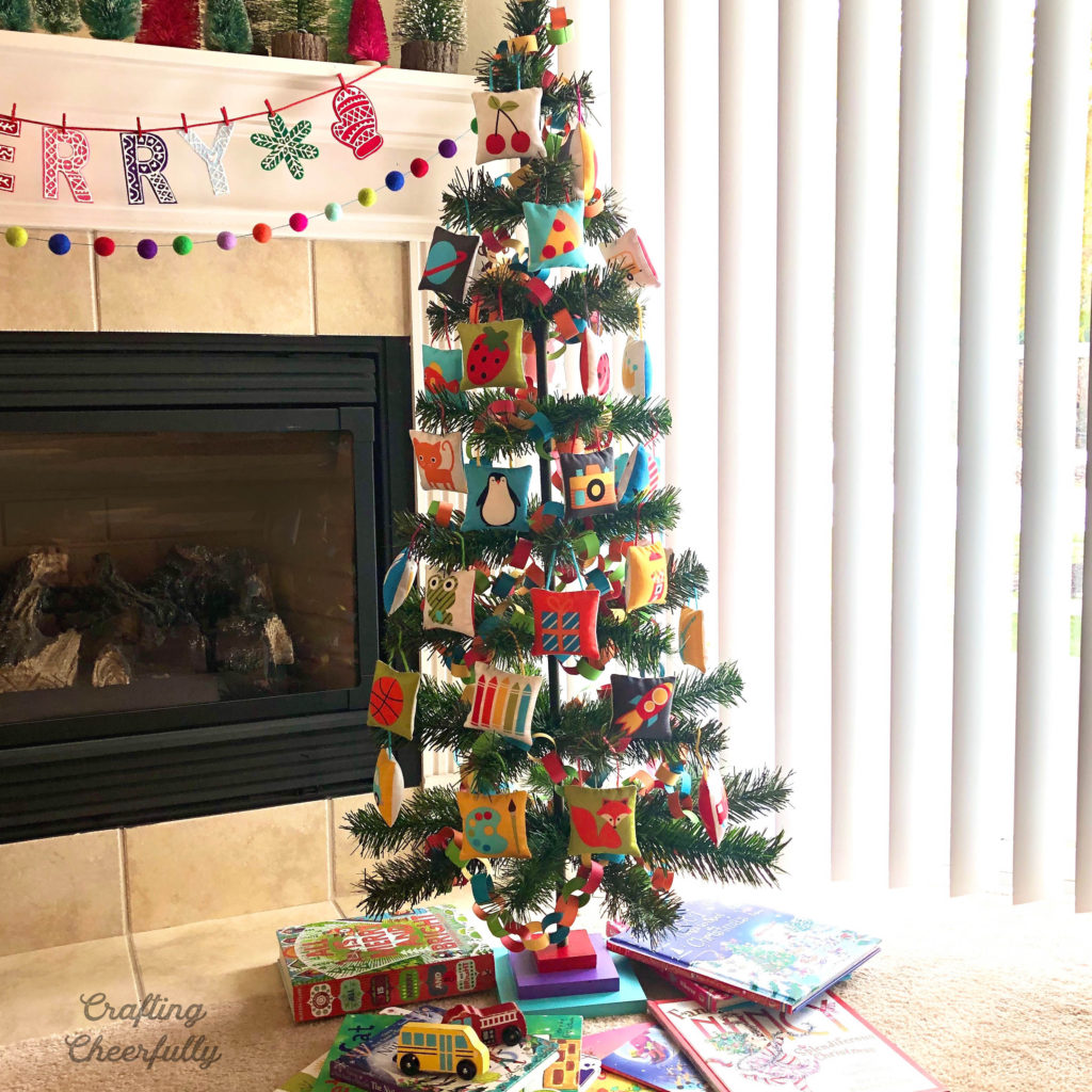 Small Christmas tree by fireplace decorated with colorful handmade pillow ornaments.