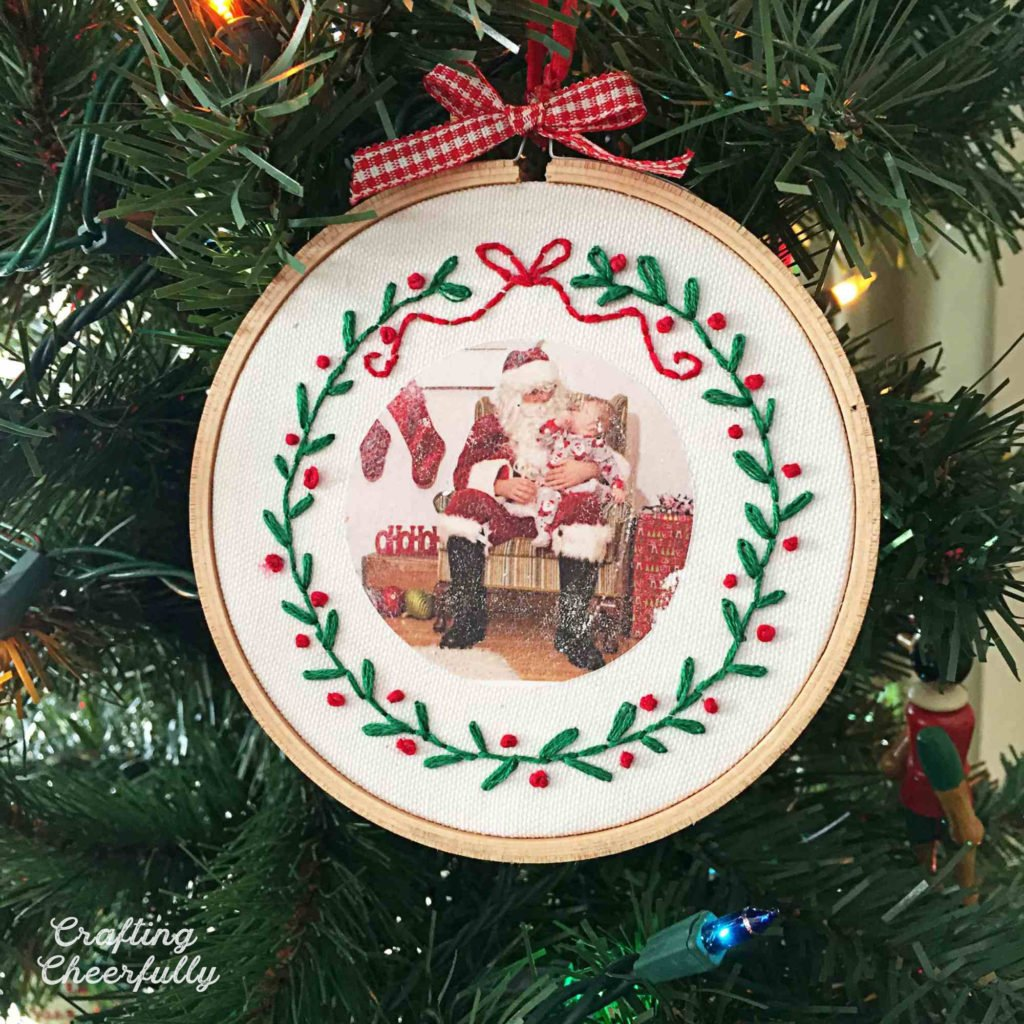Ornament made from an embroidery hoop hangs in a Christmas tree. A picture of a boy on Santa's lap is printed on fabric with a hand embroidered wreath stitched around it.