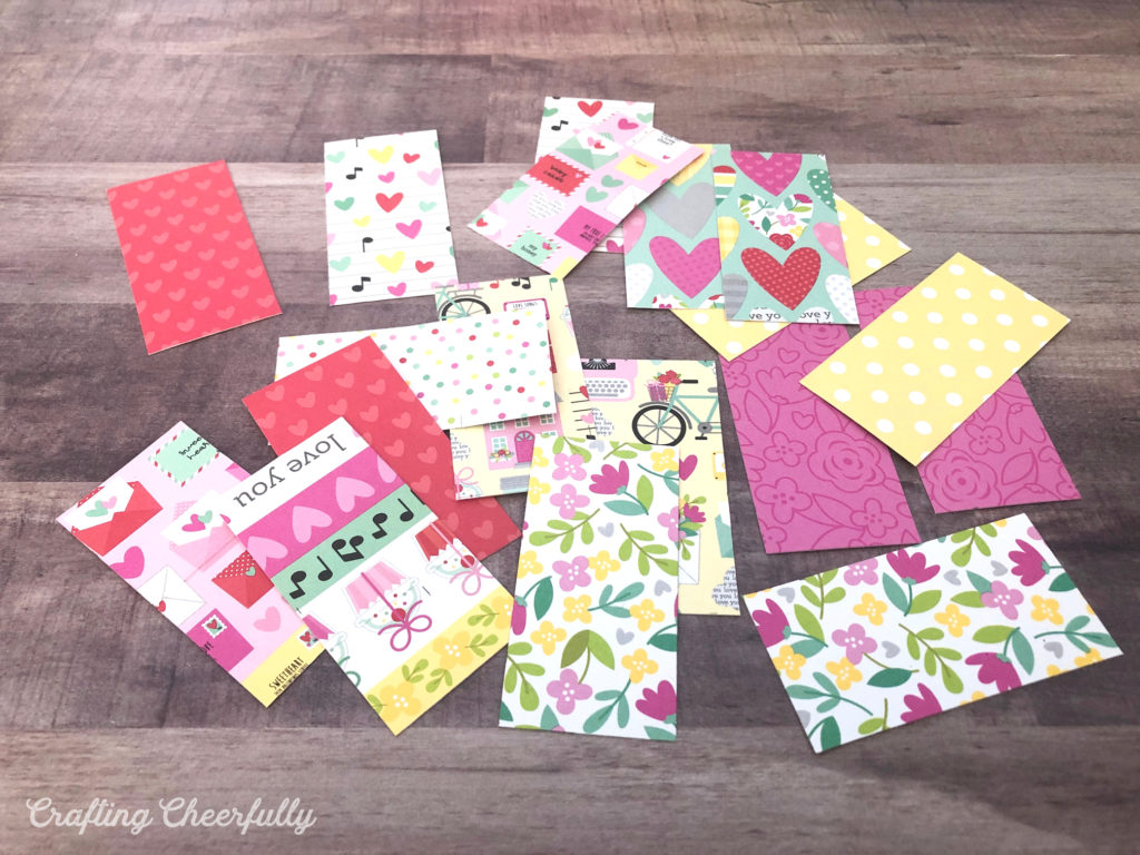 Small pieces of paper lay on a wooden table. They will be the flaps for the Valentine's Day Countdown.