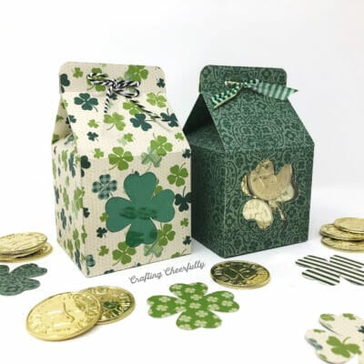 Green St. Patrick's Day milk carton treat boxes with shamrock windows sit next to gold coins and paper shamrocks.
