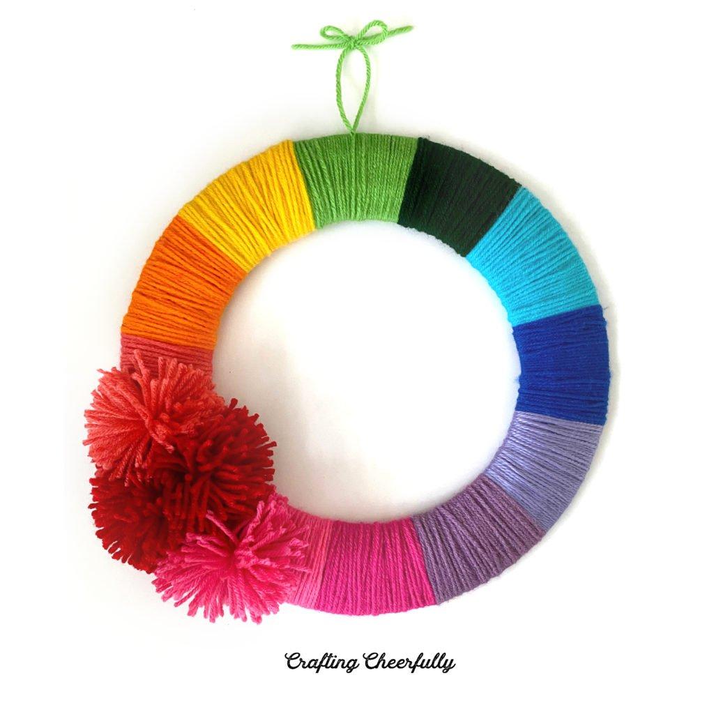 Rainbow wreath made with yarn and pom poms.