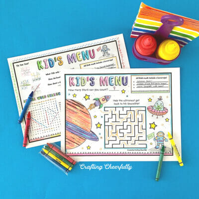 Printable Kids menus on a blue surface with crayons.