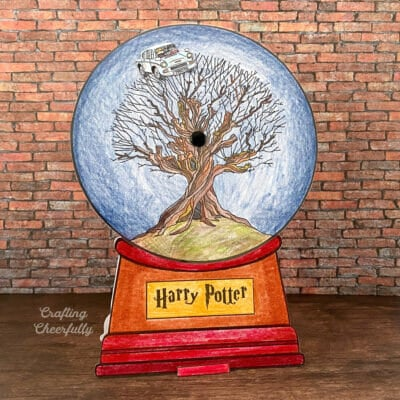 Harry Potter snow globe card standing up in front of a brick backdrop on a wooden table.