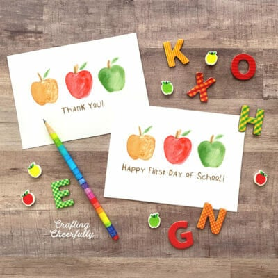 Cards featuring watercolor apples lay on a wooden table with letters, apple erasers and a pencil.