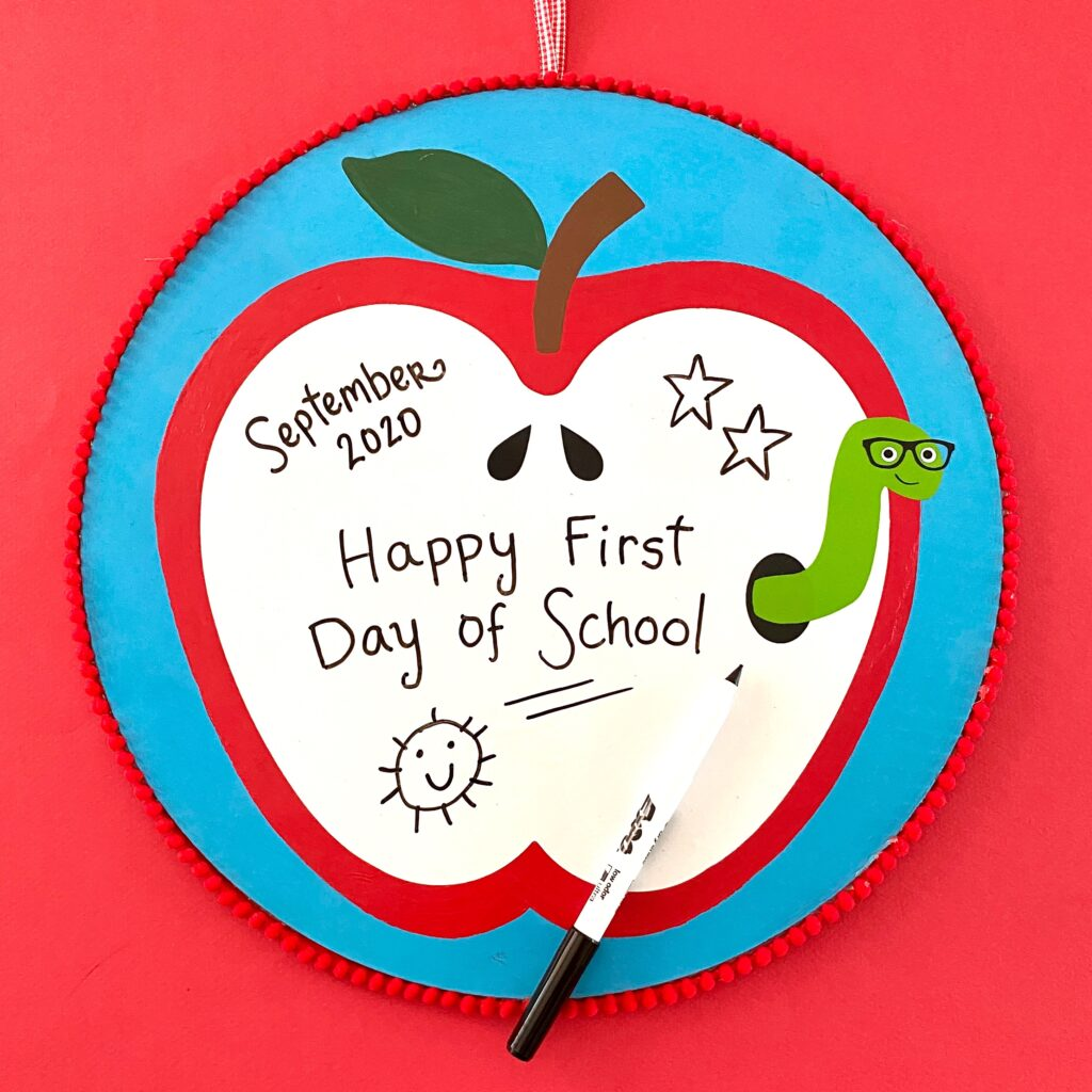 Apple dry erase board with a cute worm on a red background.