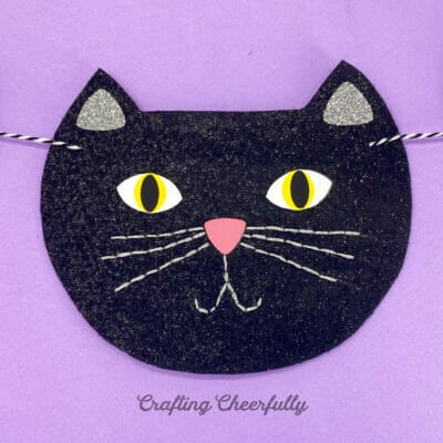 Felt black cat face on a purple background.