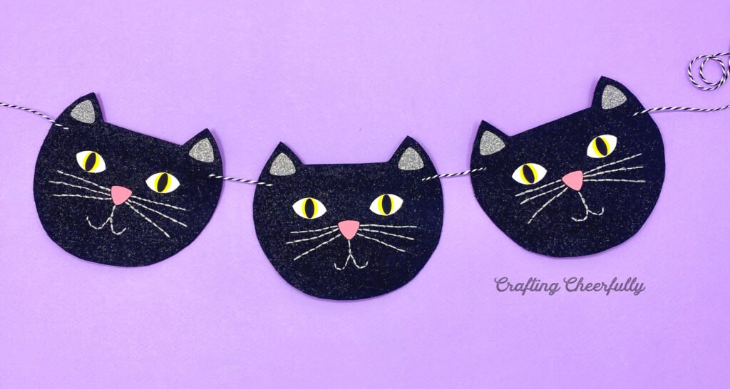 Black cat banner with three black cats strung together with a purple background.