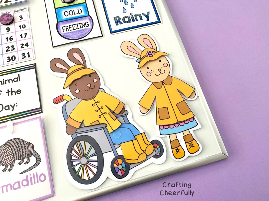 Two bunnies, one in a wheelchair and one standing, are dressed for the rain in yellow raincoats and boots!