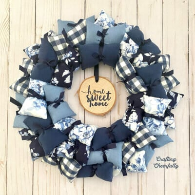 "Handmade pillow wreath in blue and white fabrics with a wood slice hanging in the center that says ""Home Sweet Home"""