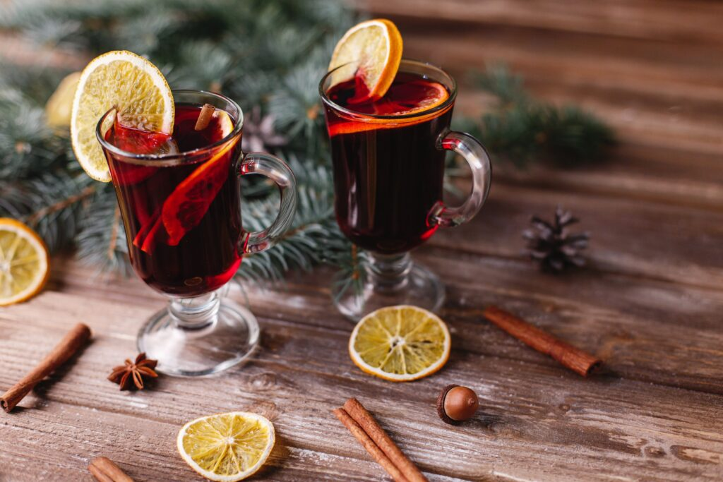 Christmas and New Year decor. Two cups of mulled wine with oranges stand on a wooden table covered with green tree branches