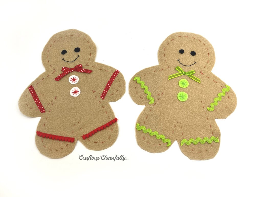Two fleece gingerbreads laying on a white table with cute trims and ribbons.