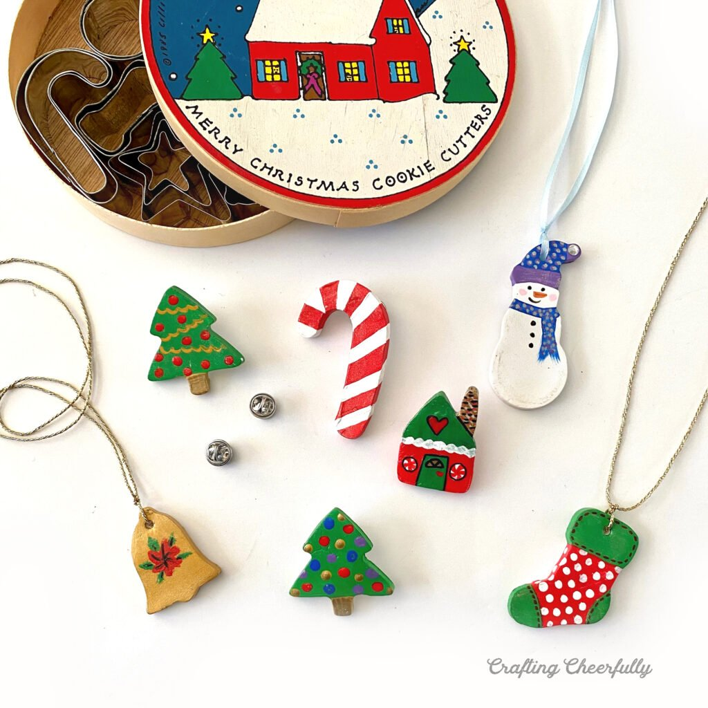 Cute Christmas jewelry handmade with air dry clay lays next to a box of mini cookie cutters.