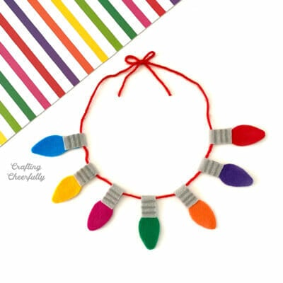 Felt holiday lights necklace on a white backgound with a piece of rainbow striped paper.