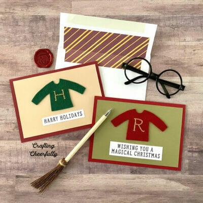 Harry Potter-themed holiday cards lay on a wooden table with a broom pen and glasses.
