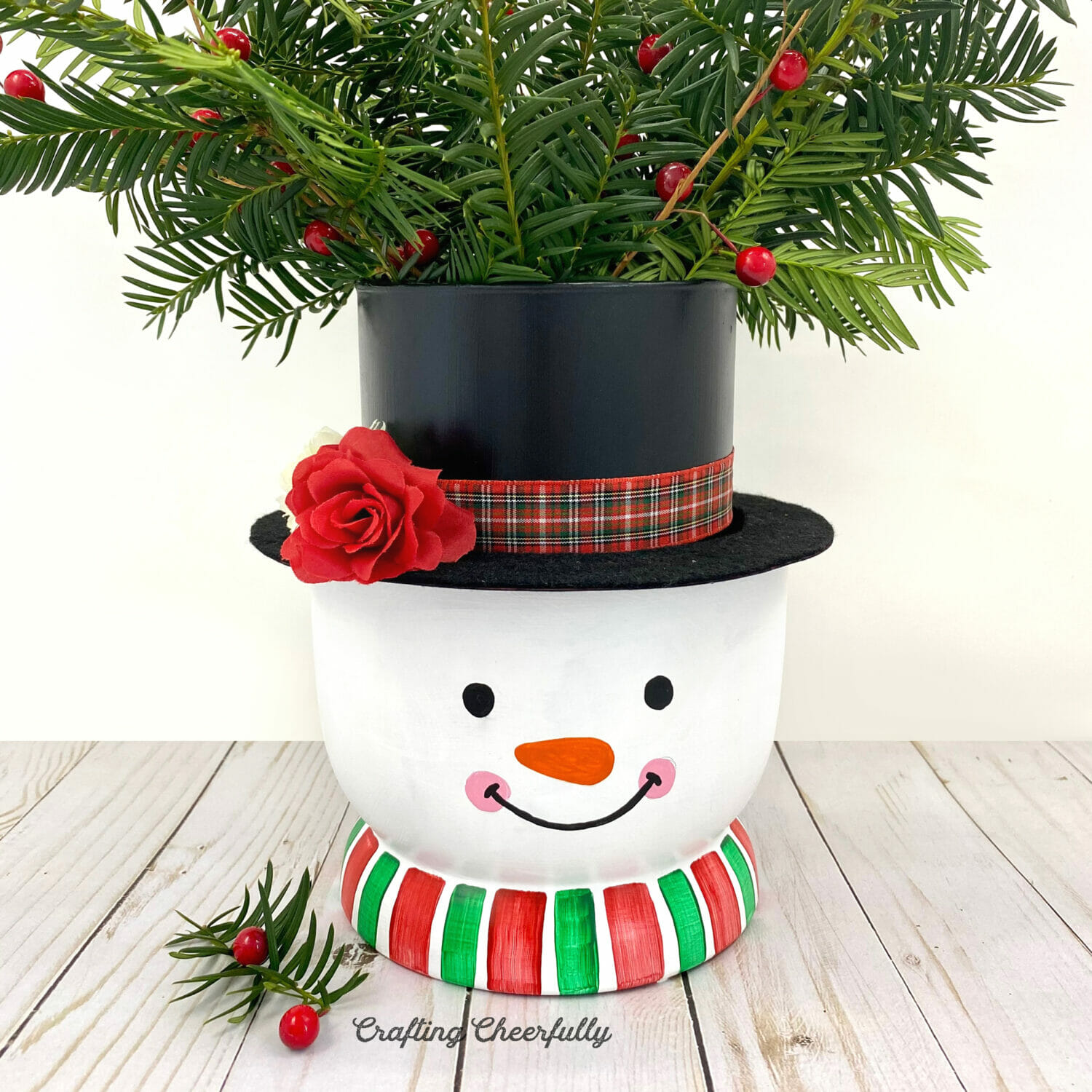 Snowman vase filled with evergreen branches sitting on a wooden table.
