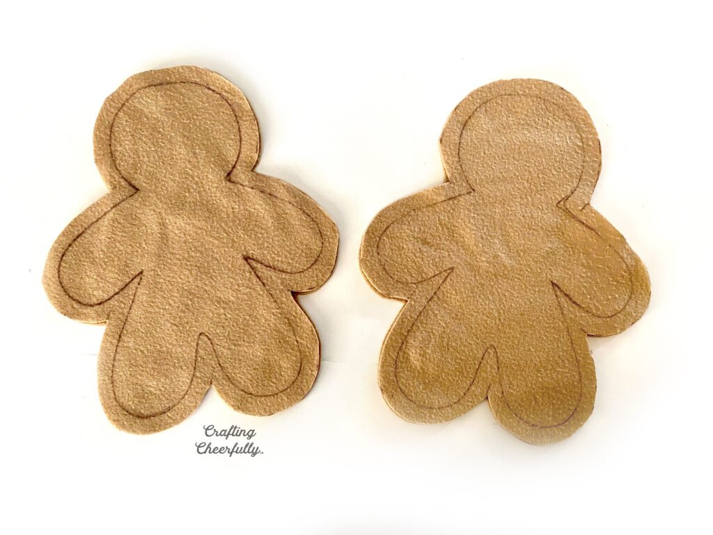 Two fleece gingerbreads cut out sitting on a white table.