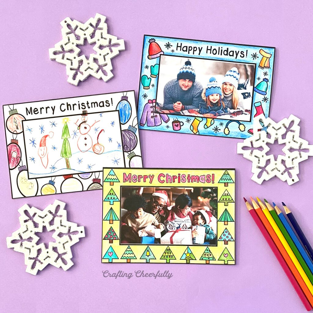Printable coloring cards laid on a purple table with colored pencils and snowflakes.
