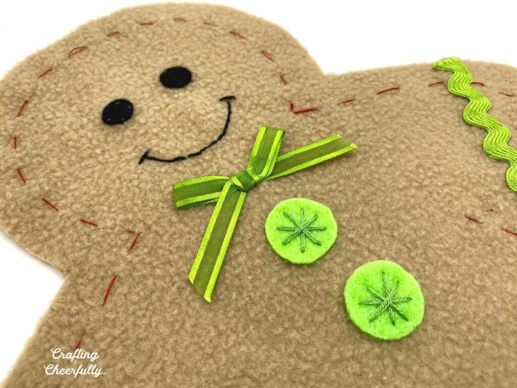 A close up picture of the first gingerbread boy with green felt buttons and a green bowtie.