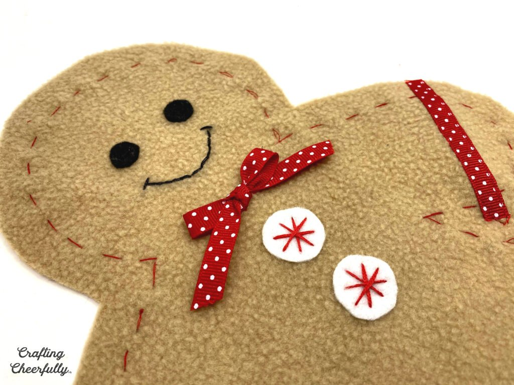 A close up picture of the girl gingerbread with white and red felt buttons and a red and white polka dot bow tie.
