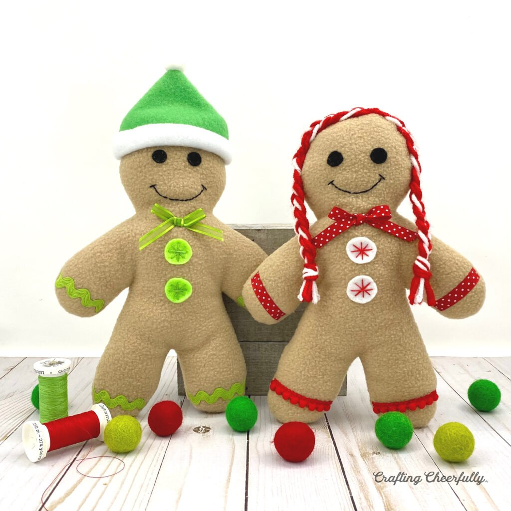 Two fleece gingerbread kids standing on a table. Both decorated with red, white and green ribbons and trims.