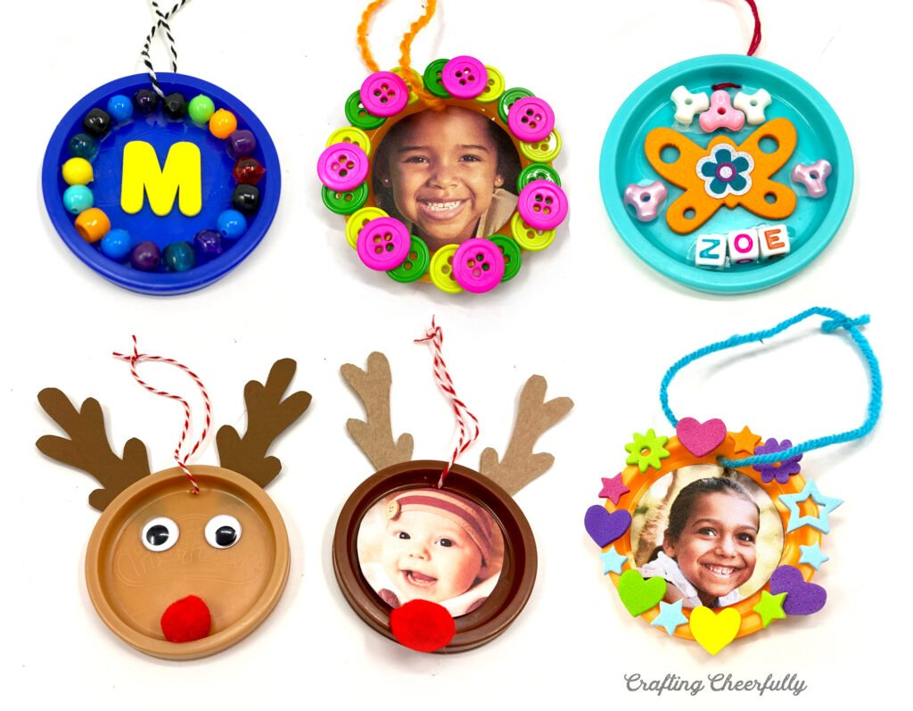 Six ornaments created from Play-Doh lids lay on a white table. Decorated with beads, pictures, reindeer antlers, googley eyes and foam stickers.
