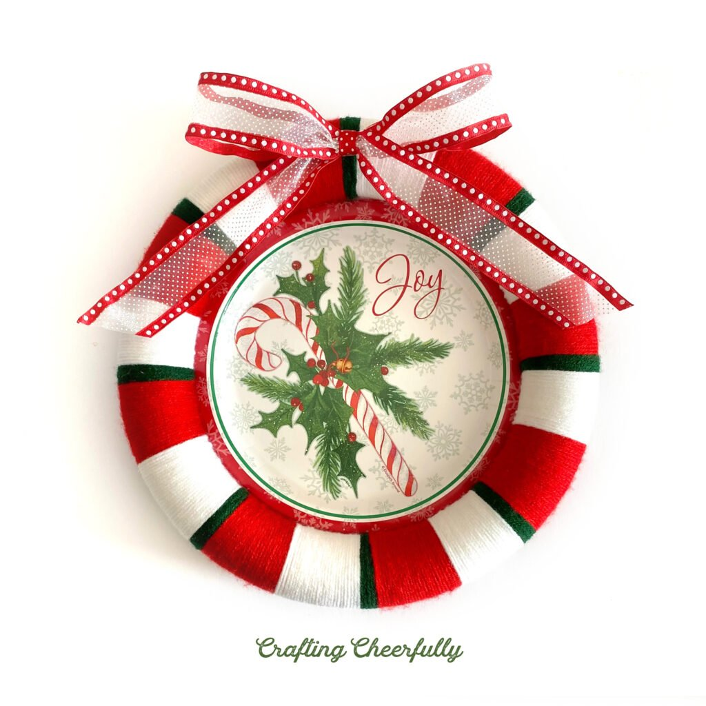 A holiday wreath made from a holiday paper plate and red, white and green yarn with a white and red bow at the top!