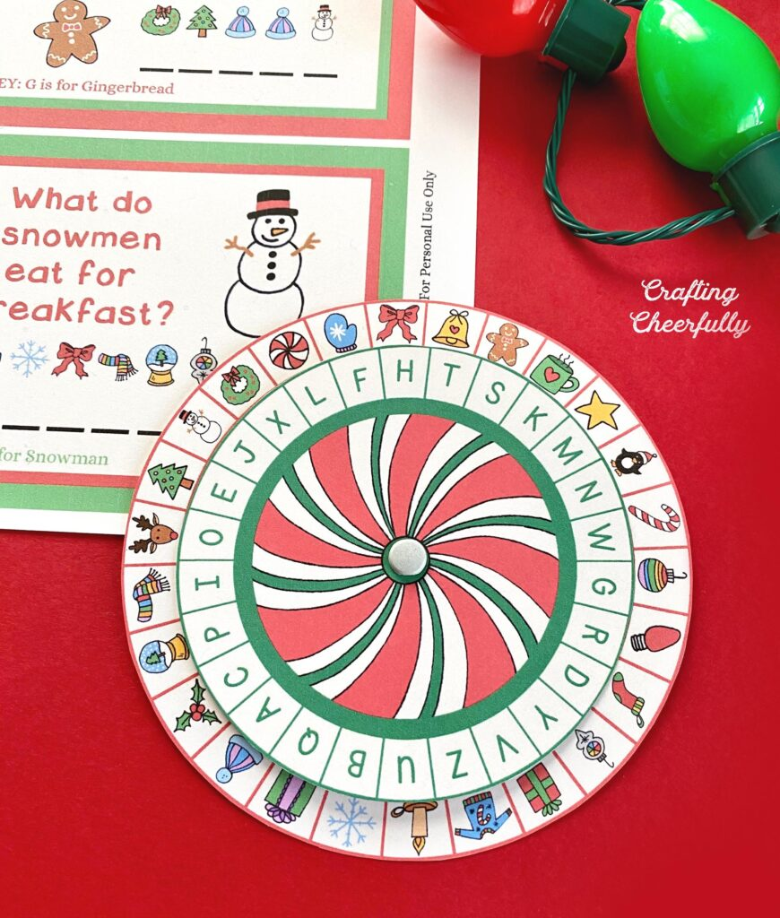 The secret decoder wheel is sitting on a red table. The wheel looks like a peppermint in the center with lots of letters and small Christmas symbols around it.