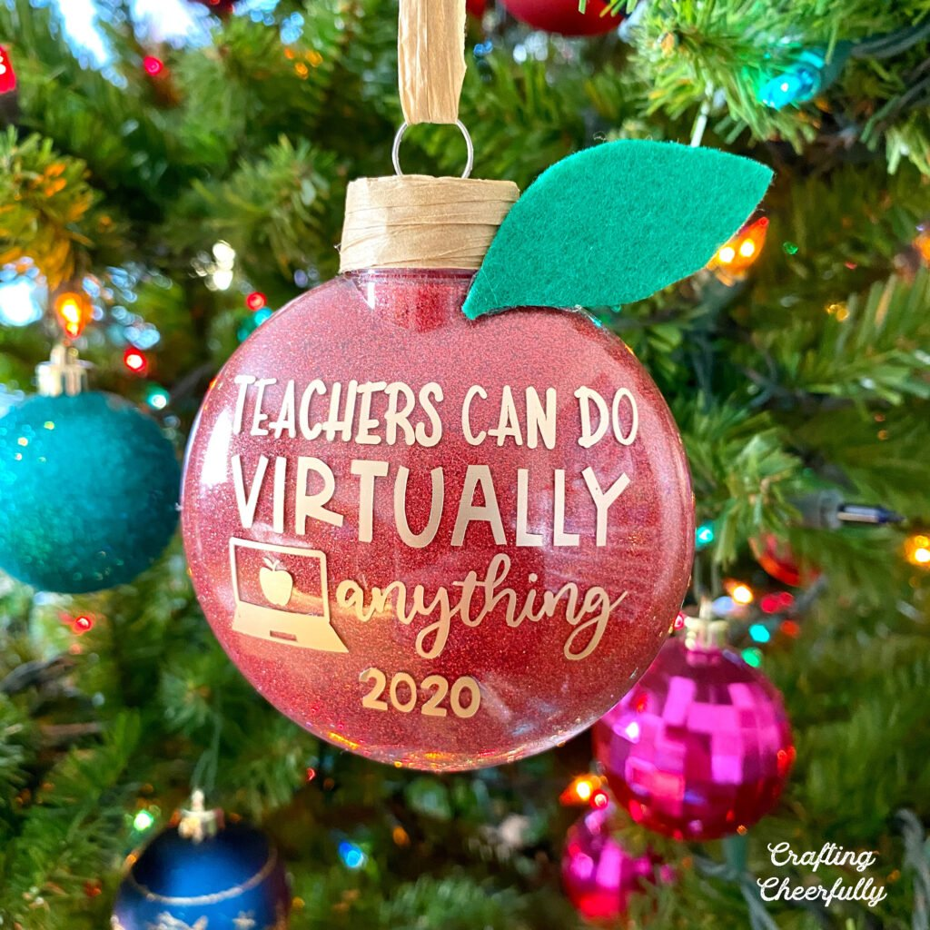 "Red glitter ornament that looks like an apple hanging in a tree with the words ""Teachers can do virtually anything"""