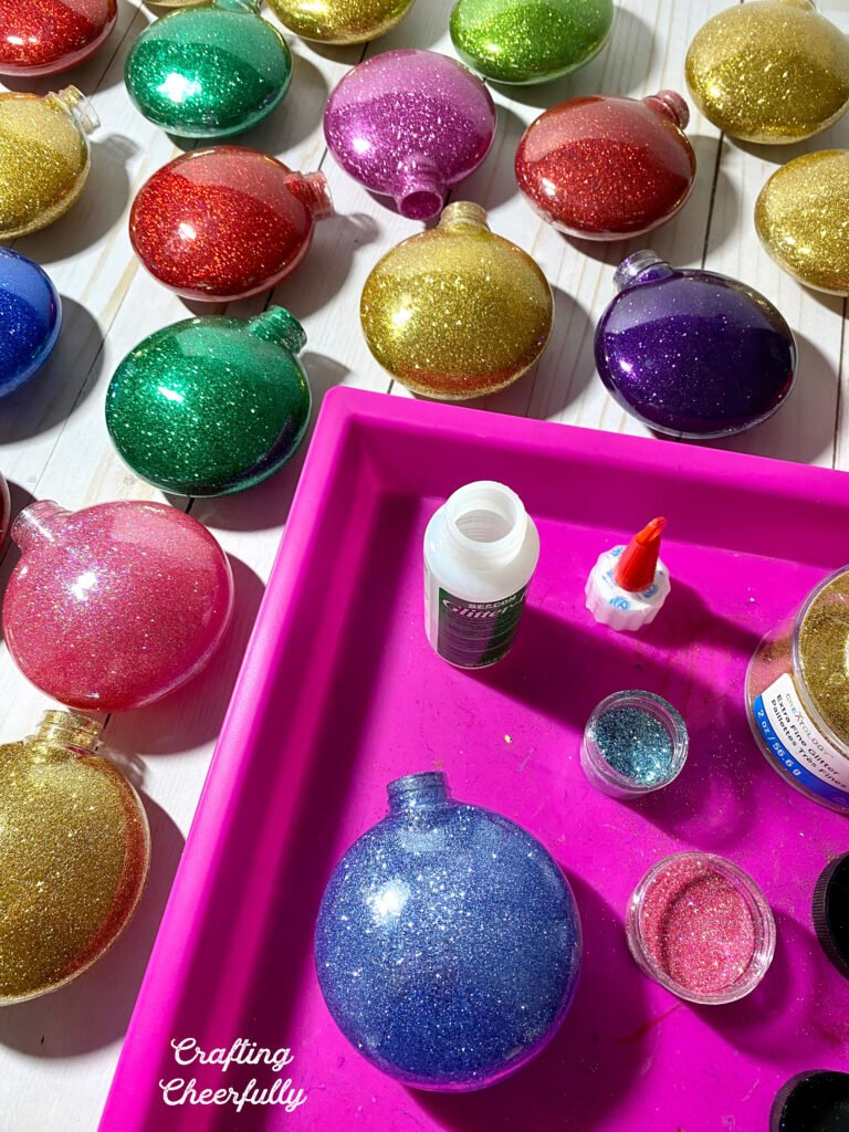 Glitter ornaments of all different colors lay on a table after being filled with Glitter-It adhesive and glitter. A pink tray holds containers of glitter.