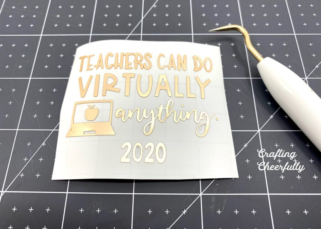 "Adhesive foil cut in the words ""Teachers can do virtually anything 2020"" laying on a black self-healing cutting mat next to a weeding tool."