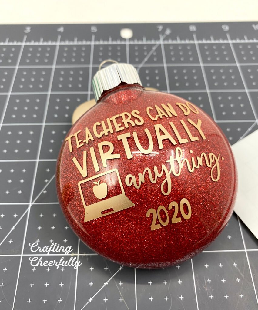 "Red ornament with gold adhesive vinyl added to it with the message ""Teachers can do virtually anything"" and the date."