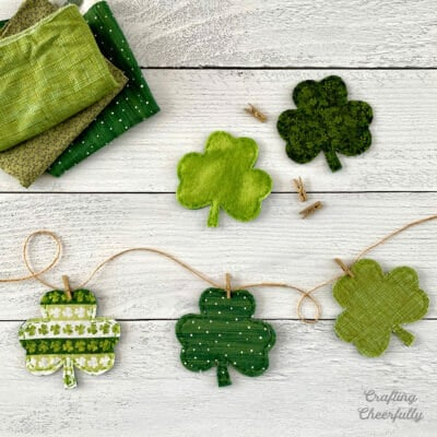 Shamrocks made from green fabric and felt strung on a banner of twine with mini clothespin.