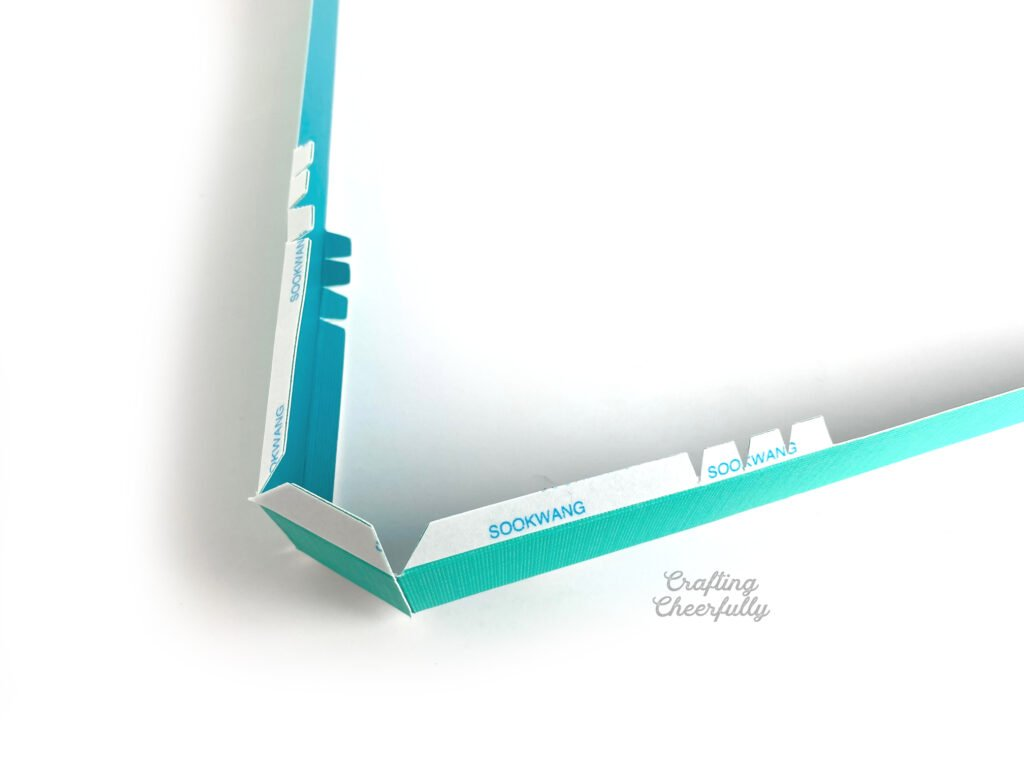 The sides of heart box are attached together with tabs folded down laying on a white table.