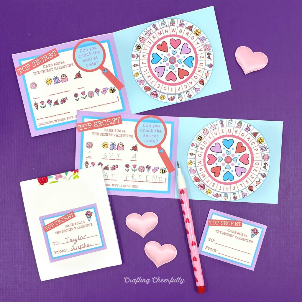 Secret Decoder Wheel Valentines on a purple table with hearts and a heart pencil.