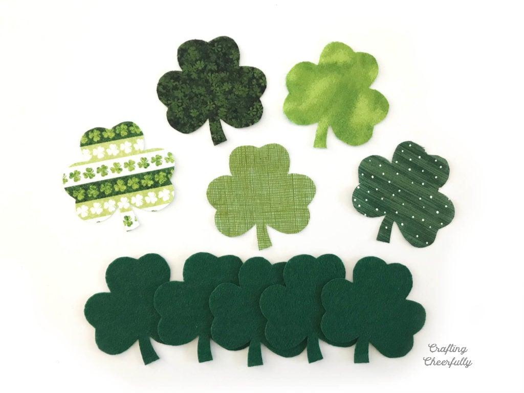 Five fabric shamrocks and five green felt shamrocks on a white background.