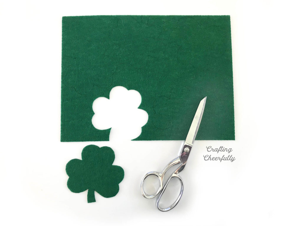 Green felt with a shamrock cut out. Gingher sewing scissors lays near the felt.