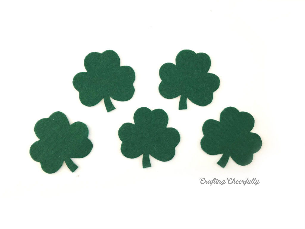 Five green felt shamrocks lay on the white table.
