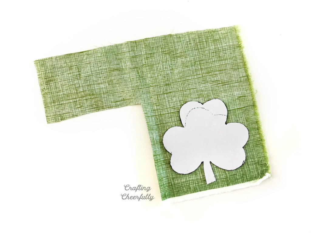 Piece of green scrap fabric with a paper shamrock template laying on one corner.