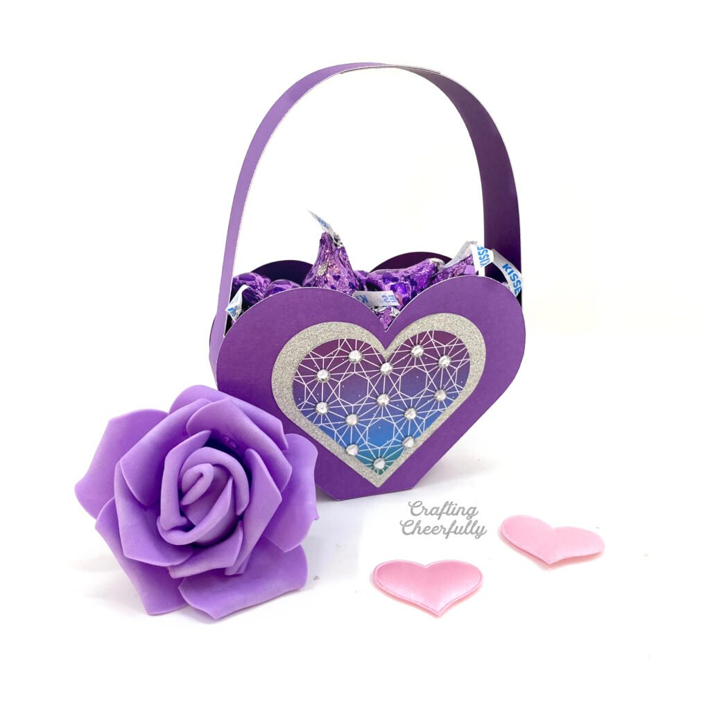 Purple heart shaped box sits on a white table. The box is filled with purple candy kisses. A purple rose sits next to the box and two pink hearts are on the table.