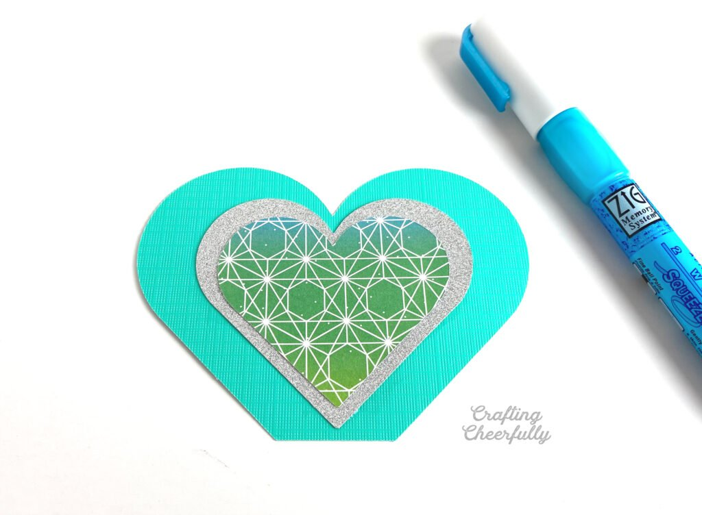 Pieces of paper shaped like hearts are layered together using glue.