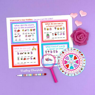 Valentine printable decoder wheel on a purple surface with pink magnifying glass and hearts and roses.